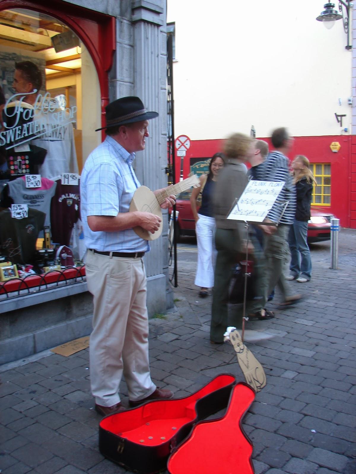 """No 2006 este """"artista"""" gañaba a vida """"tocando"""" na rúa principal de Galway co seu instrumento de cartón ollando unha partitura que só poñía """"plink plonk"""". Era un """"play-back"""" á cara, sen enganar a ninguén, e tamén recibía os seus estipendios). ¡E o seu can non ensuciaba (foto XMLS 2006)"""