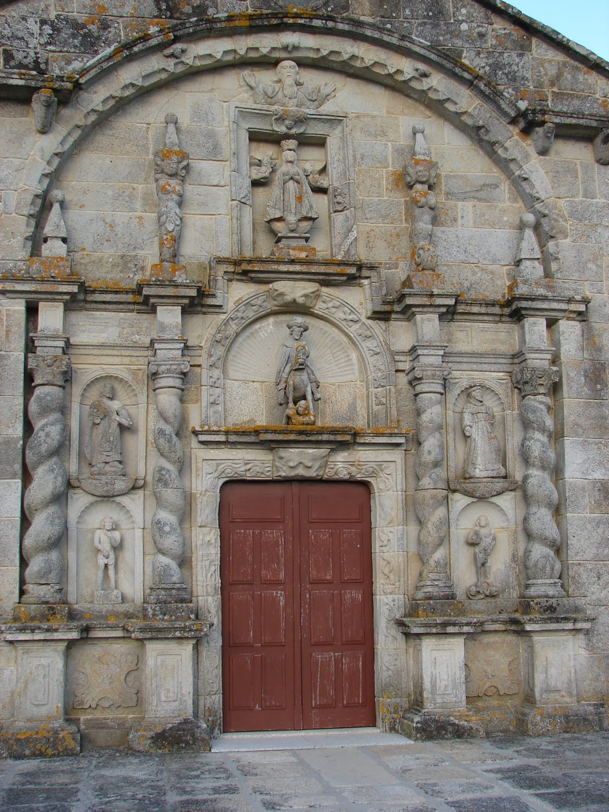 Fachada-retablo da igrexa de Traba (1716), coas imaxes do Padre Eterno e da Inmaculada (no ático); Santiago cabaleiro (centro) e, ós lados,  san Pedro e san Francisco, Adán e Eva [foto X.Mª Lema]