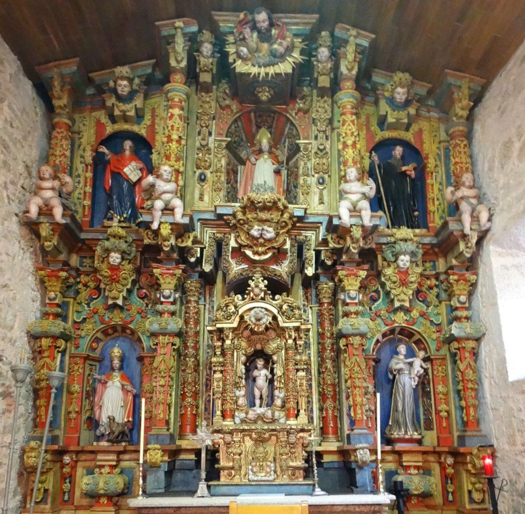 Monumental retablo barroco de San Martiño de Riobó, de dous corpos e tres paneis en cada un deles. Imaxes do Padre Eterno no ático; arriba: san Xoán Evanxelista, san Martiño (patrón) e S. Bieito; abaixo: santo Eutelo, neno Xesús e santo Antonio (foto X.Mª Lema, 2020)